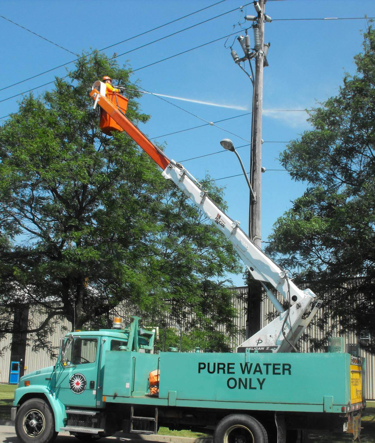 K-Line water truck with employee in bucket spraying hydro pole