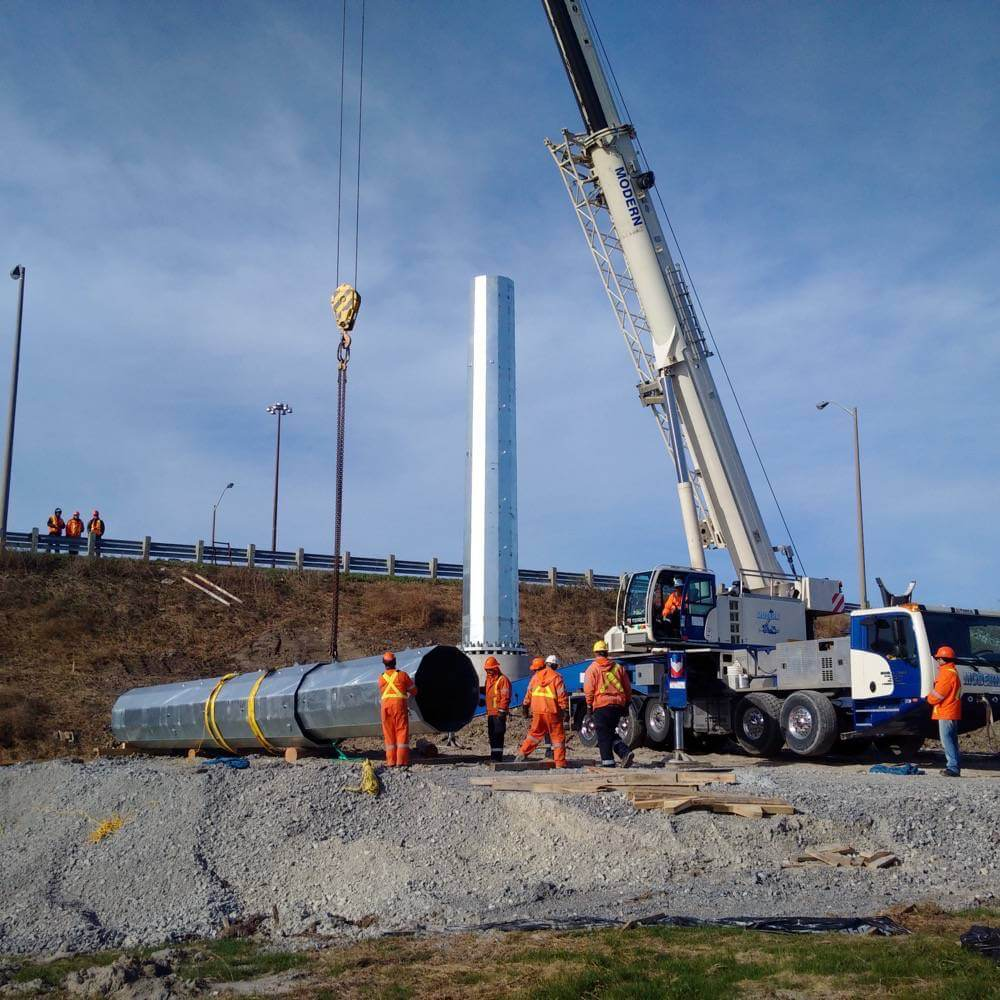 Crane lifting large pole with workers assisting