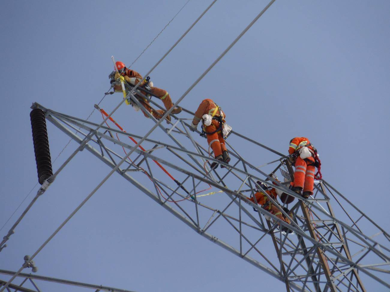Workers high up on transmission tower