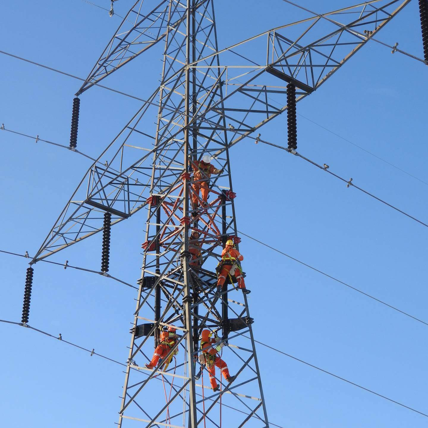 5 workers on a transmission tower
