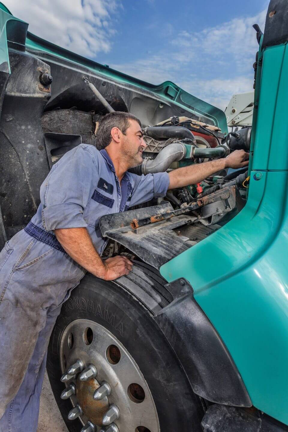 Employee working on a K-Line truck under the hood
