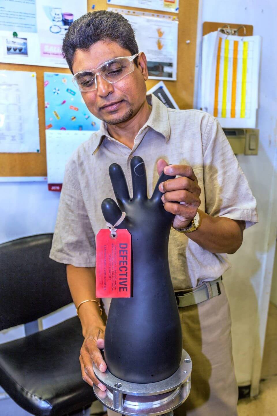 Lab employee inspecting rubber gloves