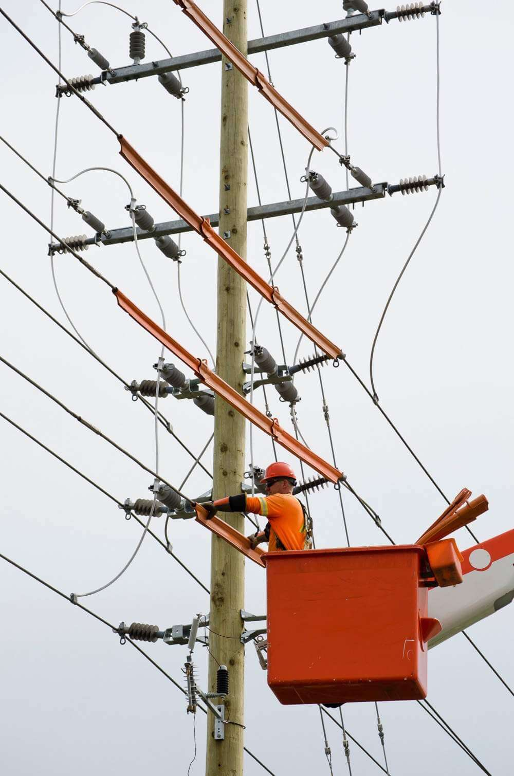 Lineman working on lines up high in bucket