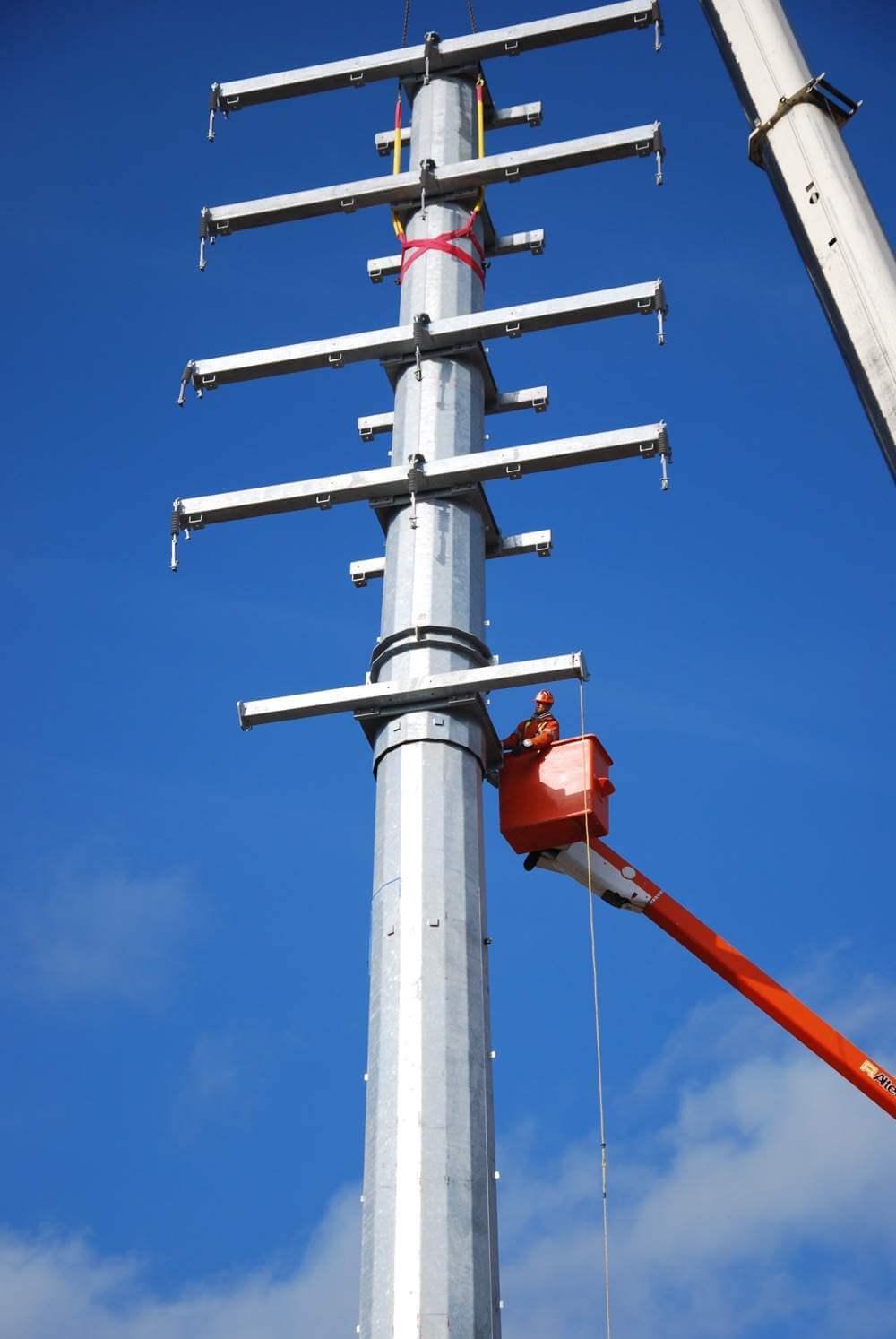 Worker up high in bucket beside pole