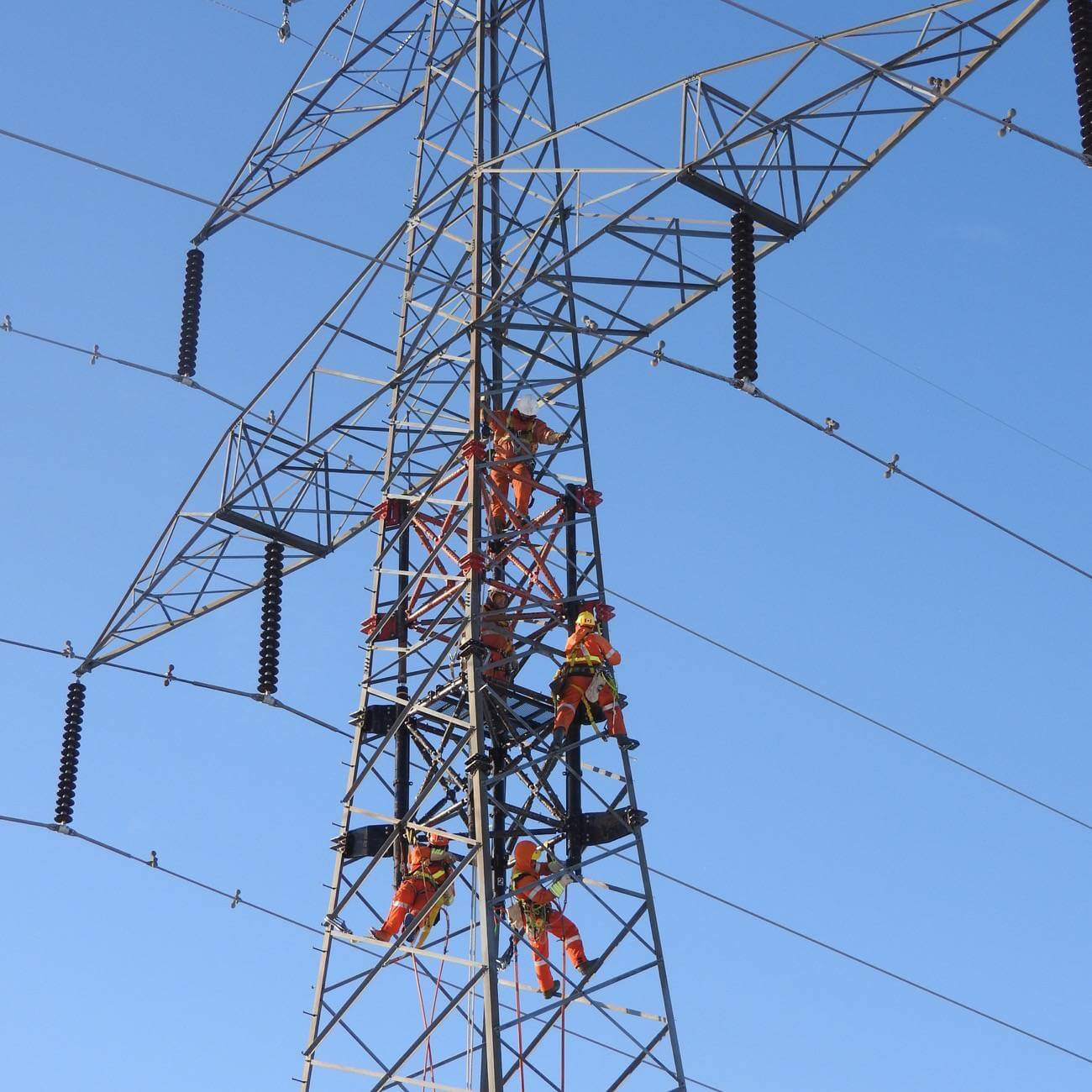 Workers up high on a transmission tower