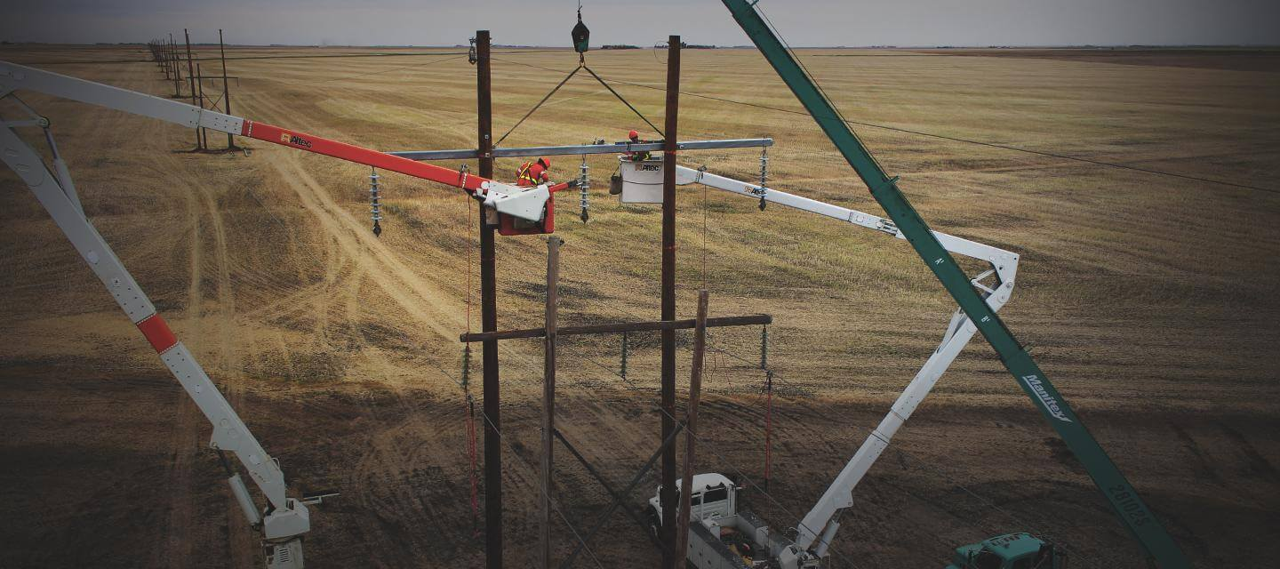 K-Line workers in buckets erecting transmission tower
