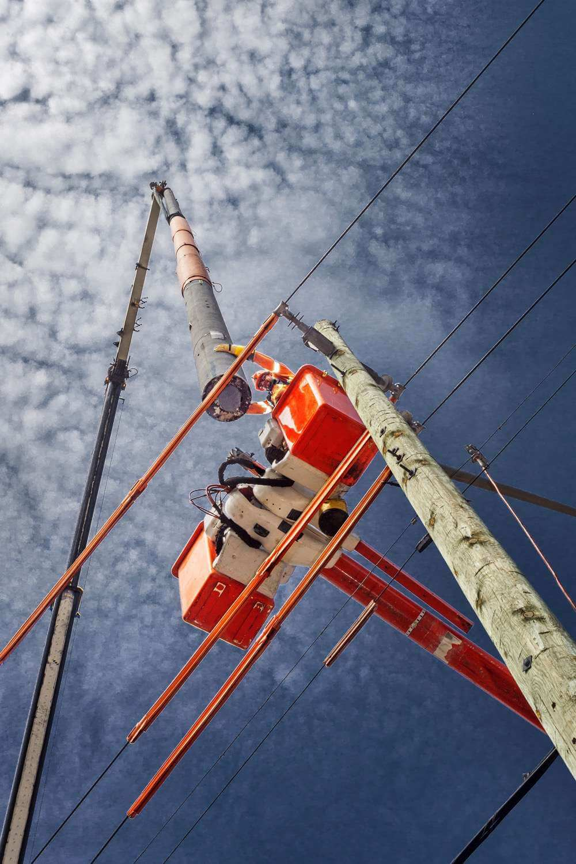 Worker high up in bucket truck helping lower hydro pole