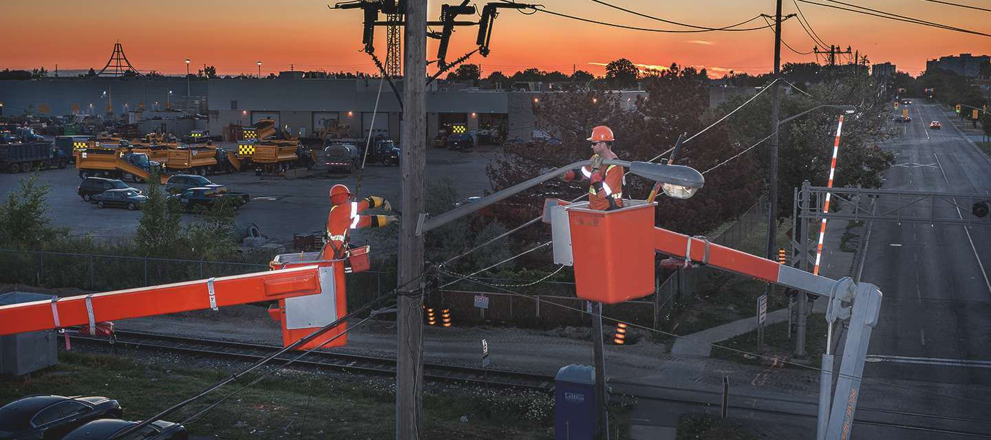 Two linemen in separate buckets doing work on streetlight attached to a hydro pole